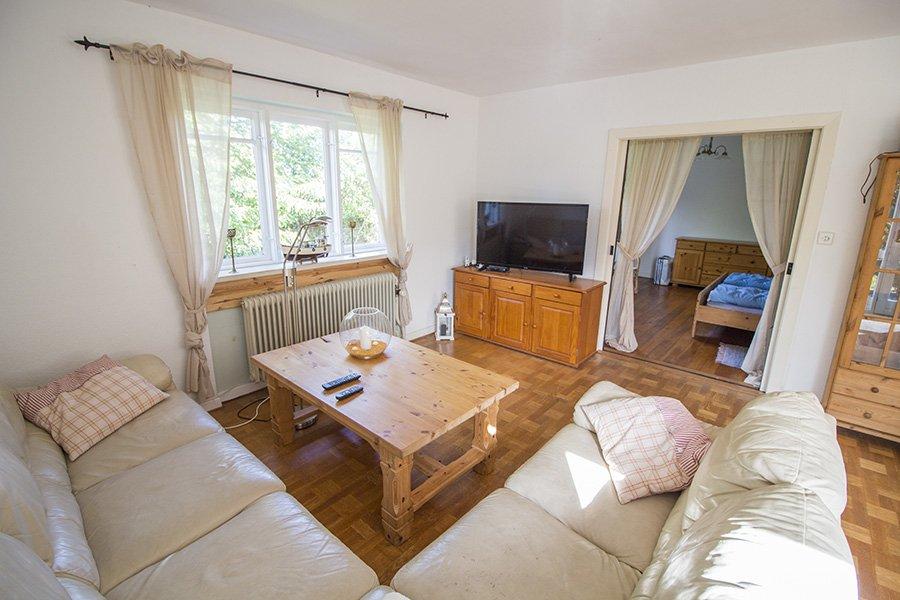 Das gemütliche Wohnzimmer mit Leder-Couchgarnitur, großem Flatscreen und deutschem TV.