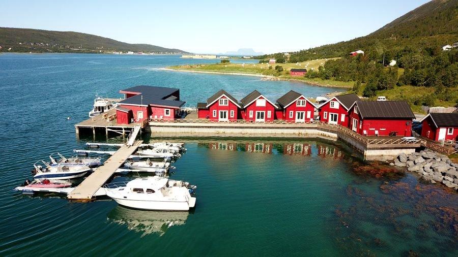 Traumhaft vor einer imposanten Bergkulisse gelegen: die roten Rorbuer des Lyngen Havfiske & Tursenters.