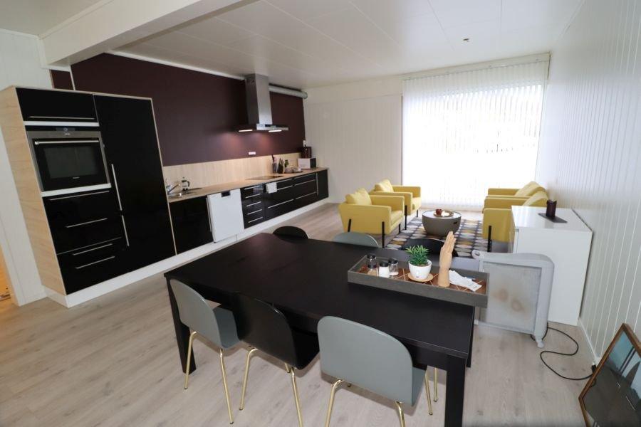 Großzügiger, offener Küchenbereich mit Esstisch und Sofagarnitur im kleinen Apartment.