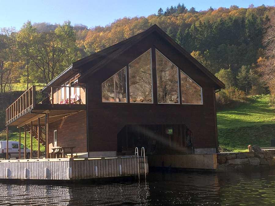 Blick vom Wasser auf das Ferienhaus und die Einfahrt in die Bootsgarage. Ihr großes Angelboot wird direkt an der Steganlage vor dem Haus angelegt werden.