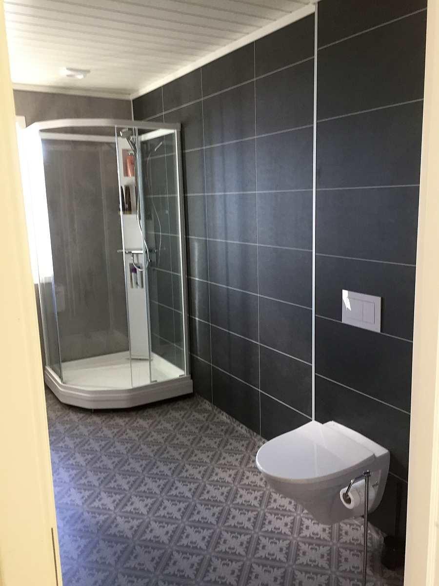Das große Badezimmer des Ferienhauses mit Dusche und WC