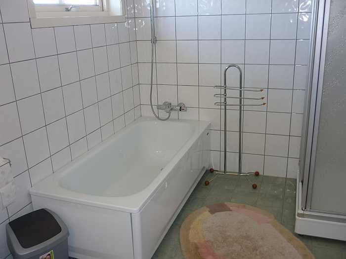 Das große Bad der Ferienwohnung mit Badewanne, Dusche WC, Doppelwaschbecken und Fußbodenheizung.