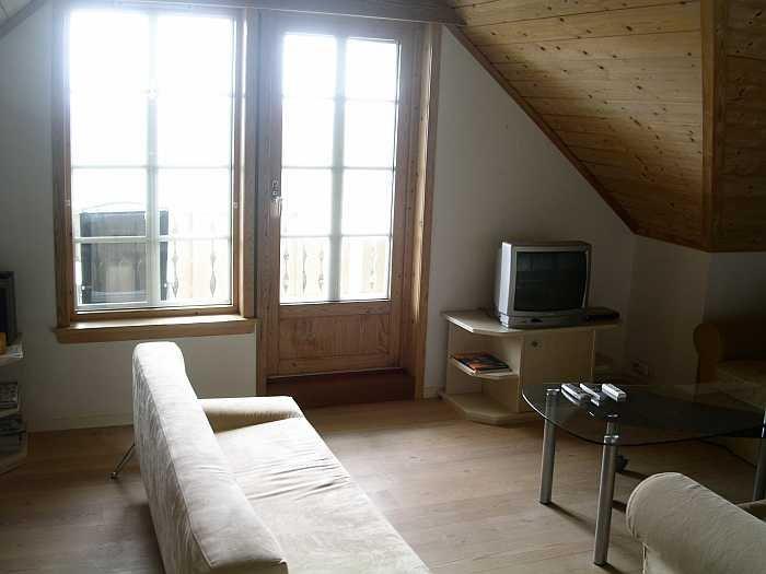 Wohnbereich der Ferienwohnung mit Zugang auf den Balkon und Blick auf das Meer
