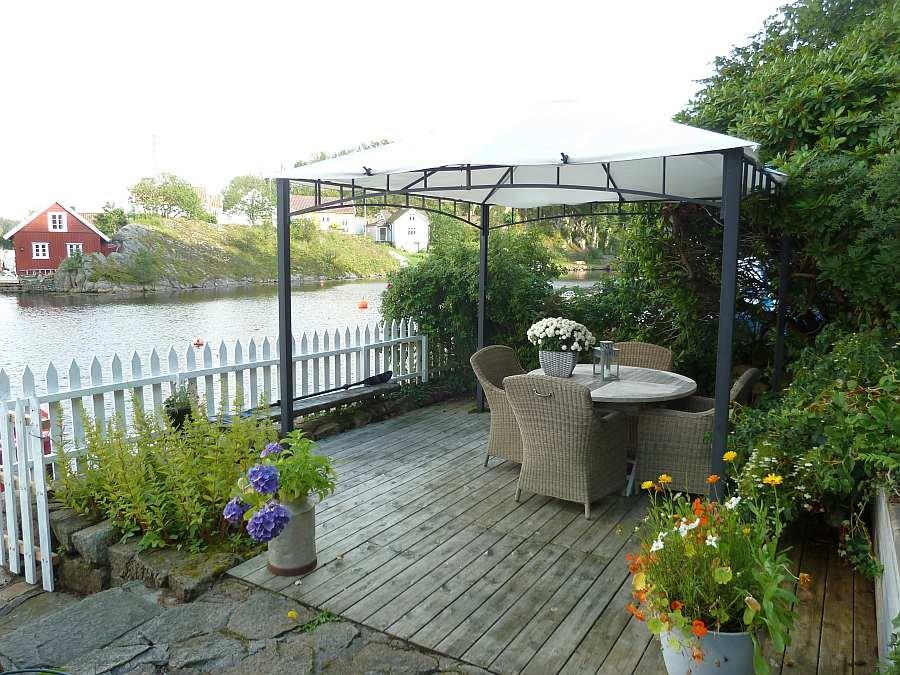 Der überdachte Terrassenbereich mit Korbsesseln und Tisch