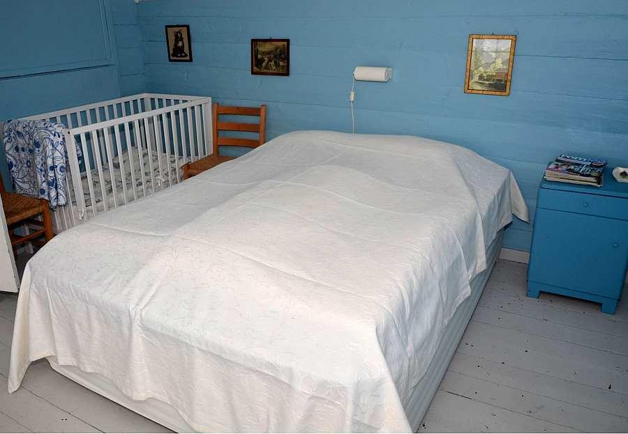 Das Doppelbett im blauen Schlafzimmer - ein Babybett ist  auch vorhanden