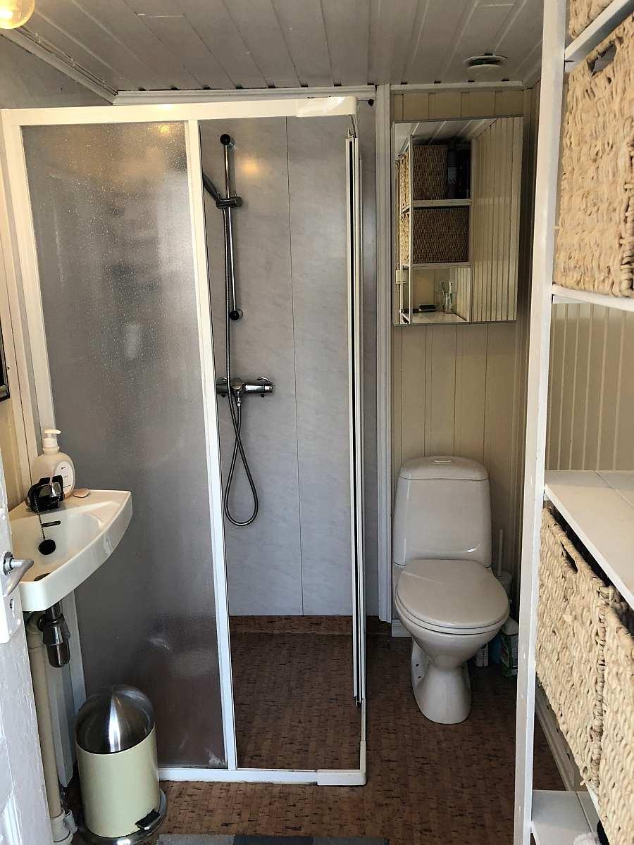 Das Badezimmer des Ferienhauses mit Dusche, Waschbecken und WC