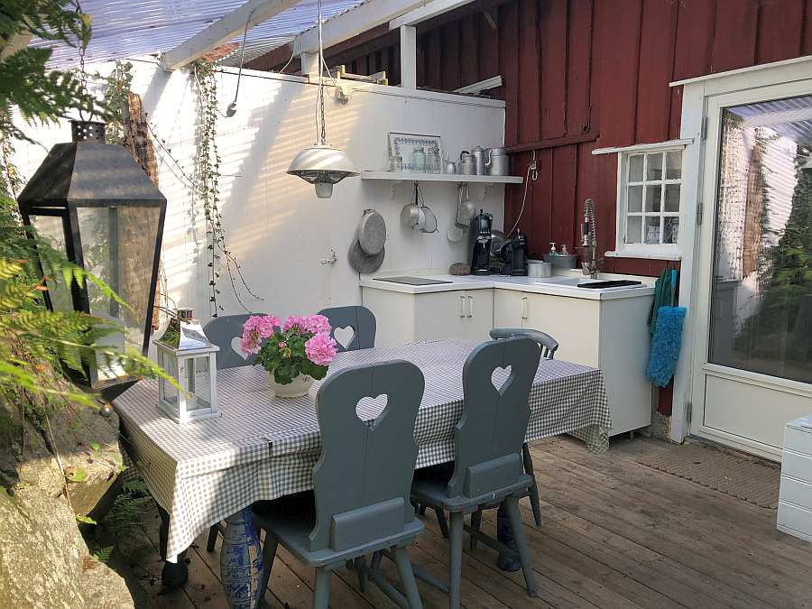 Die überdachte Außenküche mit weiterem Esstisch an der Rückseite des Hauses