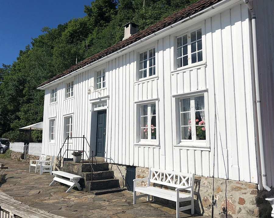 Blick auf die Vorderseite des Hauses direkt am Fjordufer - auf den Bänken kann man wunderbar die Seele baumeln lassen und auf den Fjord blicken. DER perfekte Platz für den ersten Kaffee am Morgen...