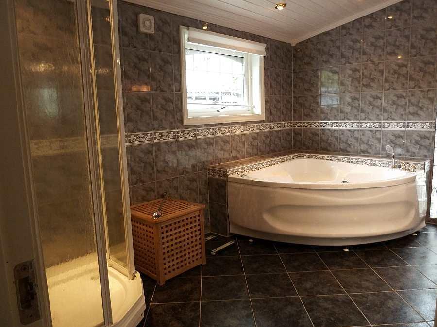 Das große Badezimmer mit Fußbodenheizung verfügt über Dusche, Waschbecken, Whirlpool und WC