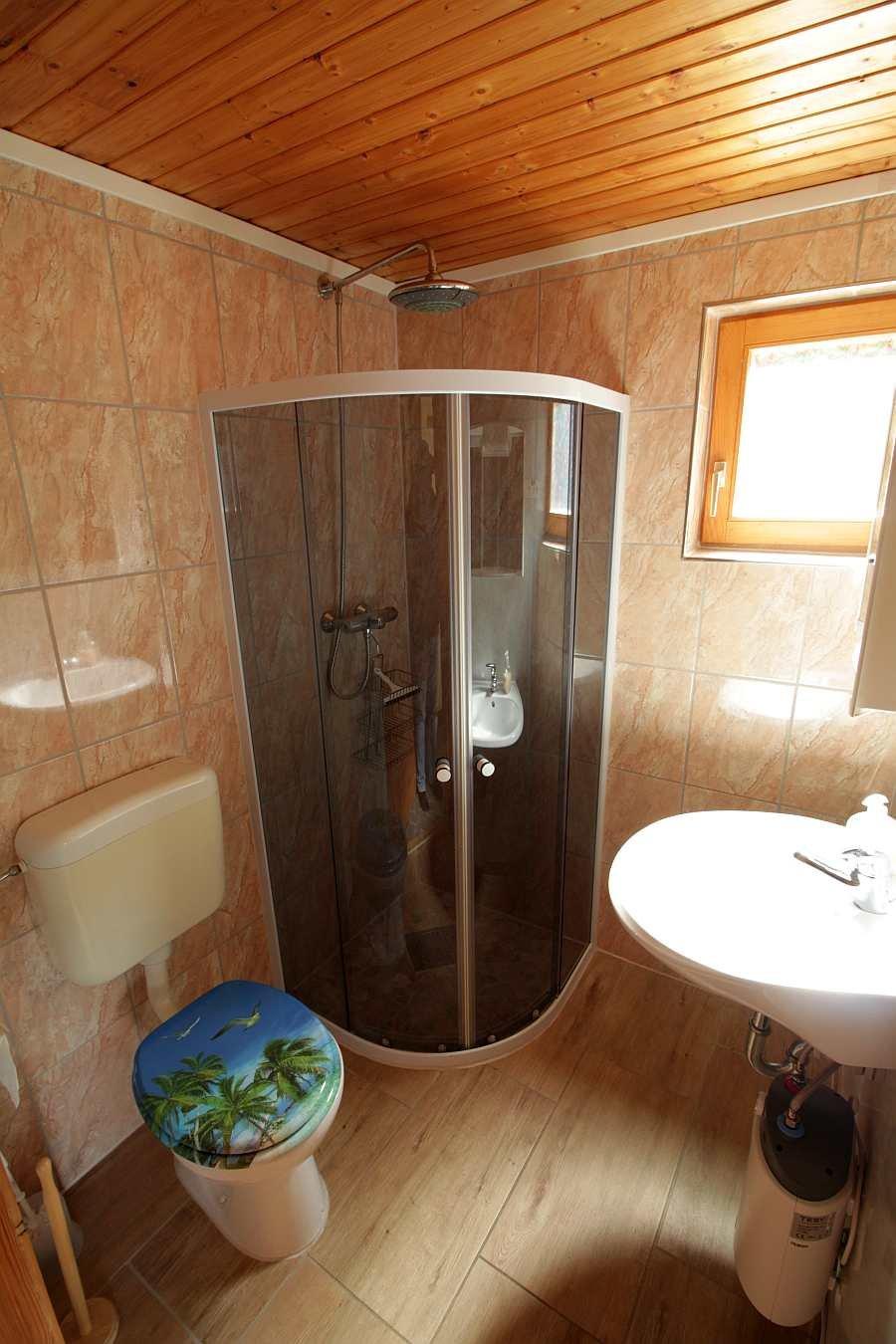 Das Badezimmer mit Dusche, Waschbecken und WC in der Wohnung im Obergeschoß