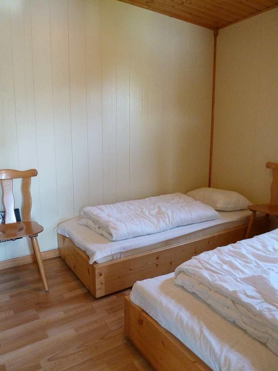 Das zweite Schlafzimmer mit drei Einzelbetten in der Wohnung im Erdgeschoß