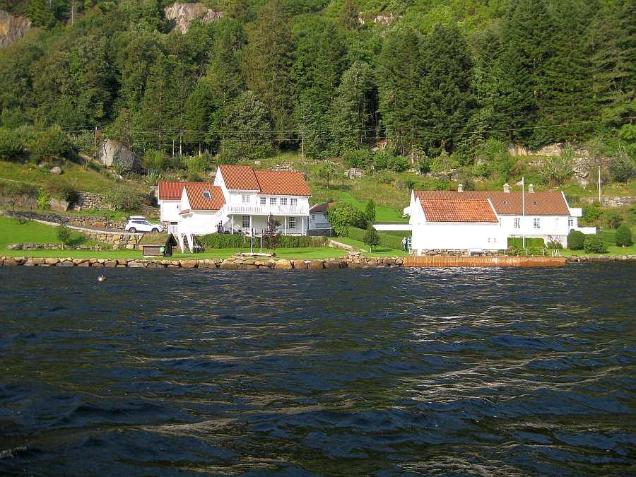 Blick vom Wasser auf das herrliche Grundstück am Fjordufer - links das Ferienhaus Sjursen, im Vordergrund rechts das Bootshaus auf dem eigenen Grundstück, ganz rechts schräg dahinter wohnt ihr Vermieter auf separatem Grundstück