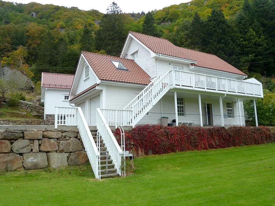 Ferieinhaus Sjursen - liegt umgeben von Bergen und Wälder. Das Gebäude im Hintergrund ist nur ein großer Schuppen.