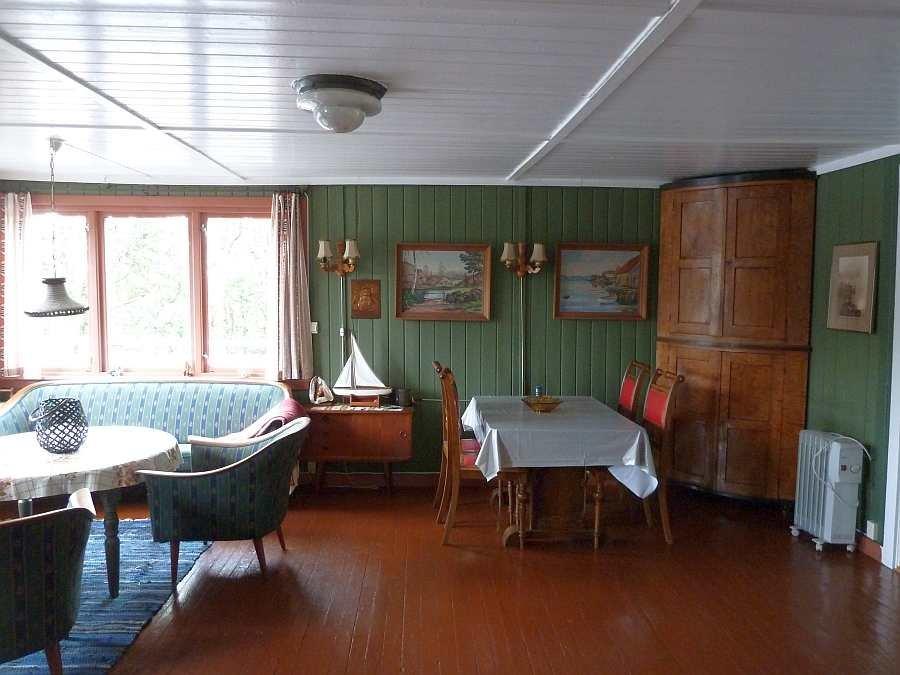 Das Wohnzimmer des Feriehauses ist stilecht mit etlichen Dingen aus den geschichtlichen Etappen des Hauses eingerichtet