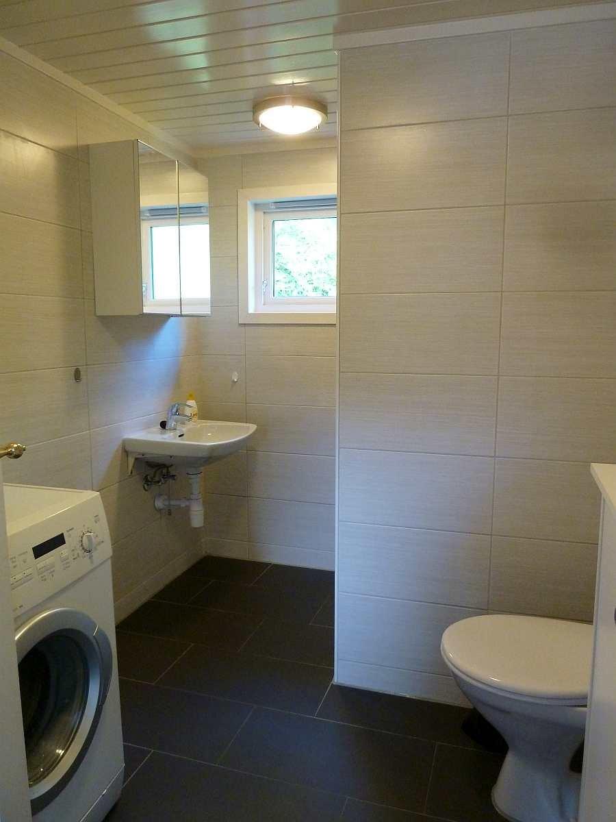 Das Badezimmer des Ferienhauses mit WC, Dusche, Waschbecken und Waschmaschine. Fußbodenheizung vorhanden.