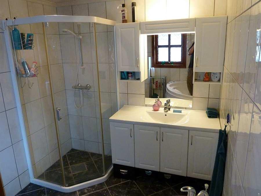 Das Badezimmer des Ferienhauses mit Dusche, WC und Waschbecken
