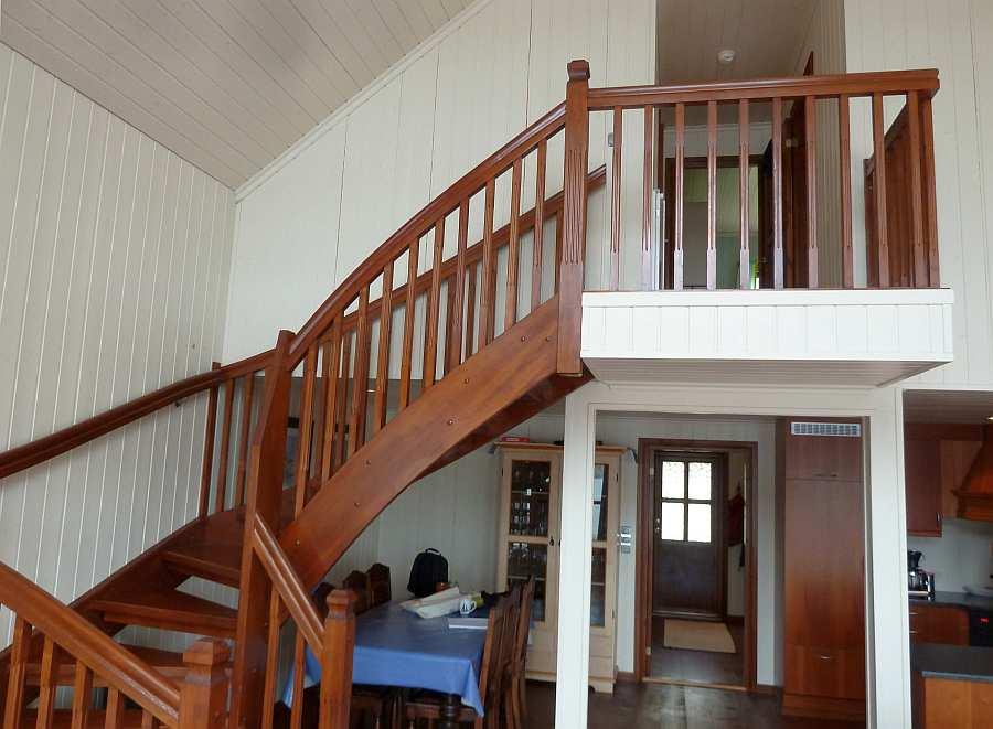 Eine Treppe führt  vom Wohnbereich hinauf auf die offene Galerie im Obergeschoß