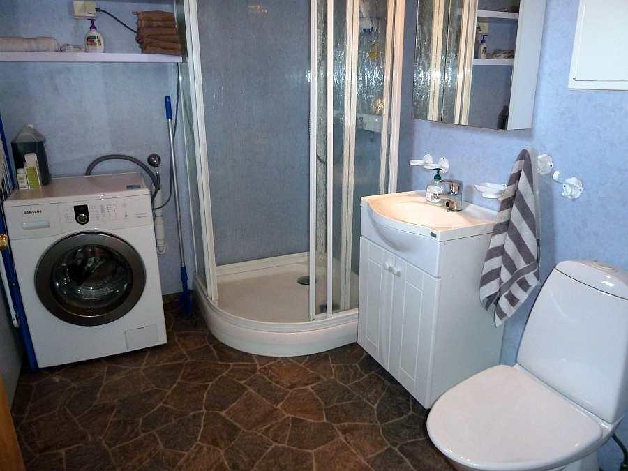 Das Badezimmer des Ferienhauses mit Dusche, Waschbecken und WC. Zusätzlich steht hier eine Waschmaschine zur Verfügung