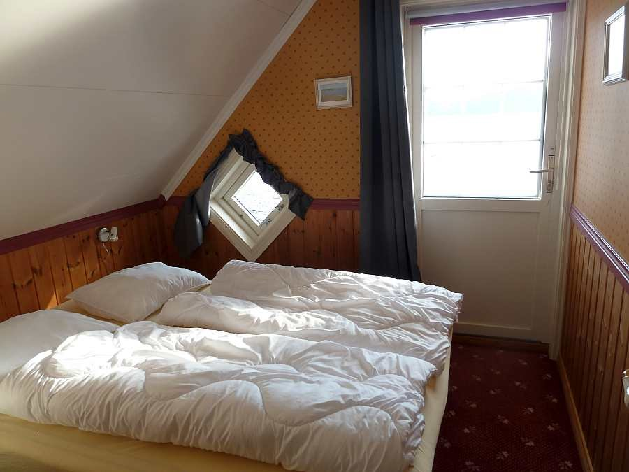 Das erste Schlafzimmer mit einem Doppelbett und Blick auf den Fjord