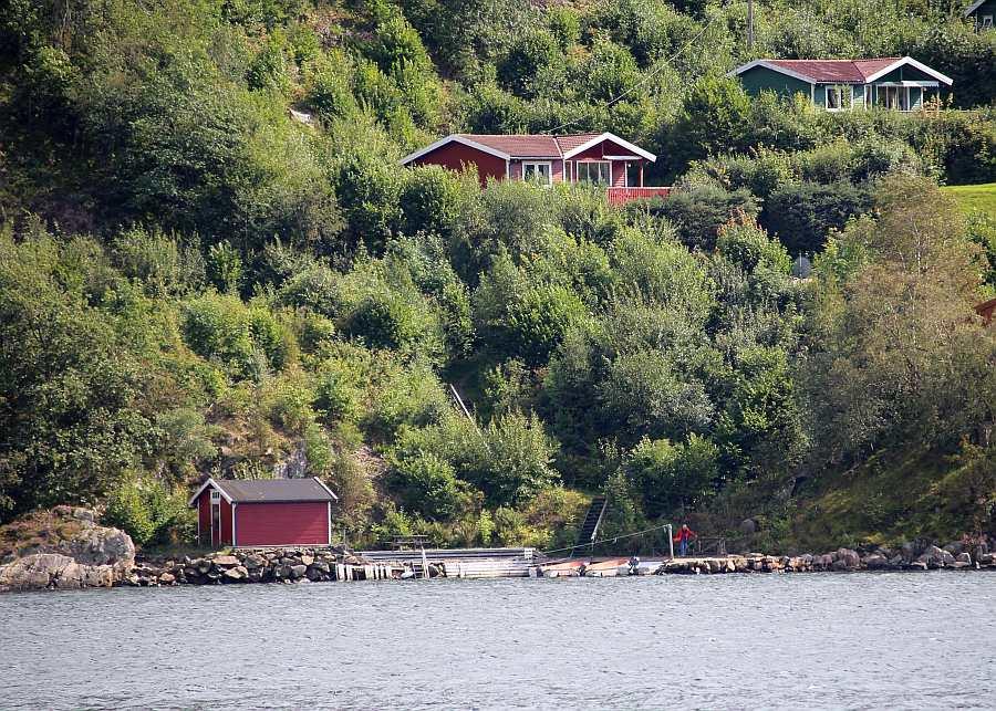 Ferienhaus Lindal (rotes Haus) liegt mit wenigen weiteren Häusern im lockeren Verbund naturnah in erhöhter Lage am Hang - ein phantastischer Weitblick über den Fjord ist hier selbstverständlich. Die Boote liegen hier direkt vor dem Haus am Steg