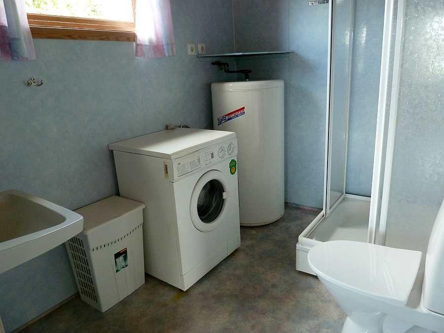 Das Bad des Hauses mit Dusche, WC und Waschbecken. Zusätzlich steht hier eine Waschmaschine zur Verfügung