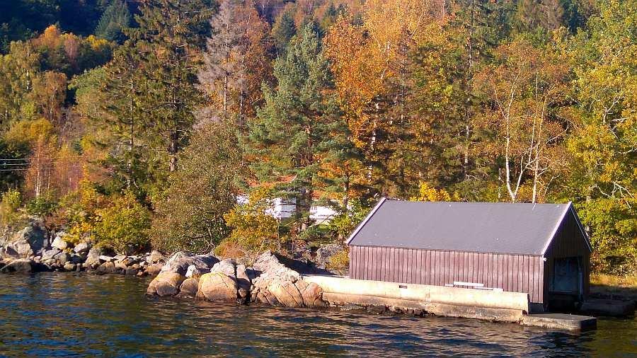 Blick vom Wasser auf das Bootshaus und das Grundtstück - im Hintergrund kann man das Wohnhaus erkennen