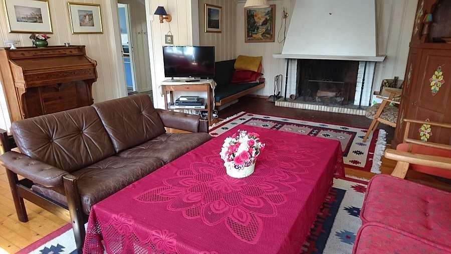 Das gemütliche Wohnzimmer des Ferienhauses. Ein Kamin und ein Sat-TV stehen zur Verfügung