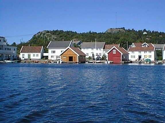 Haus Svinør liegt unmittelbar am Wasser  (weißes Haus zwischen gelbem und rotem Bootshaus)