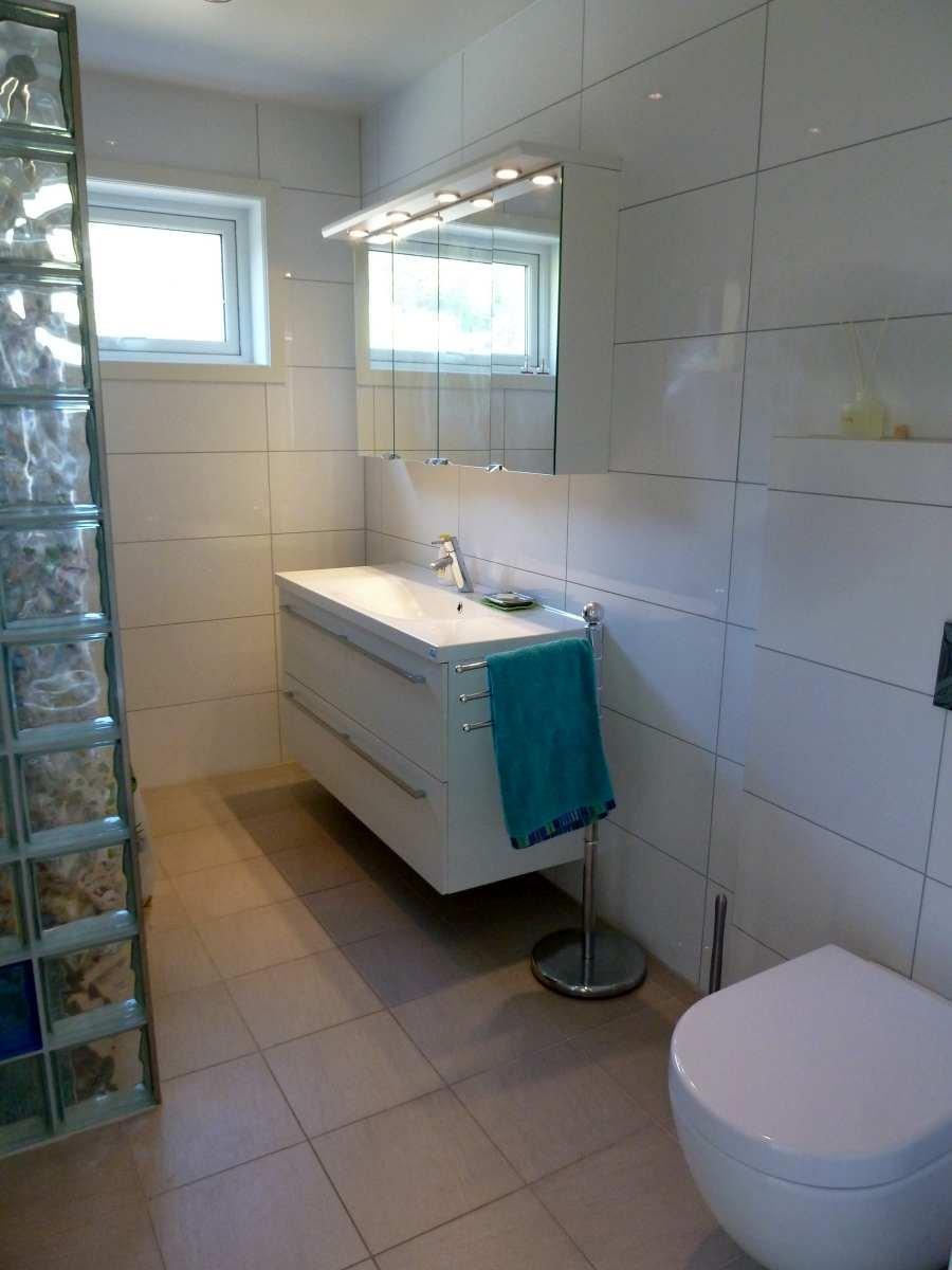 Das erste Badezimmer mit Waschtisch, Dusche und WC