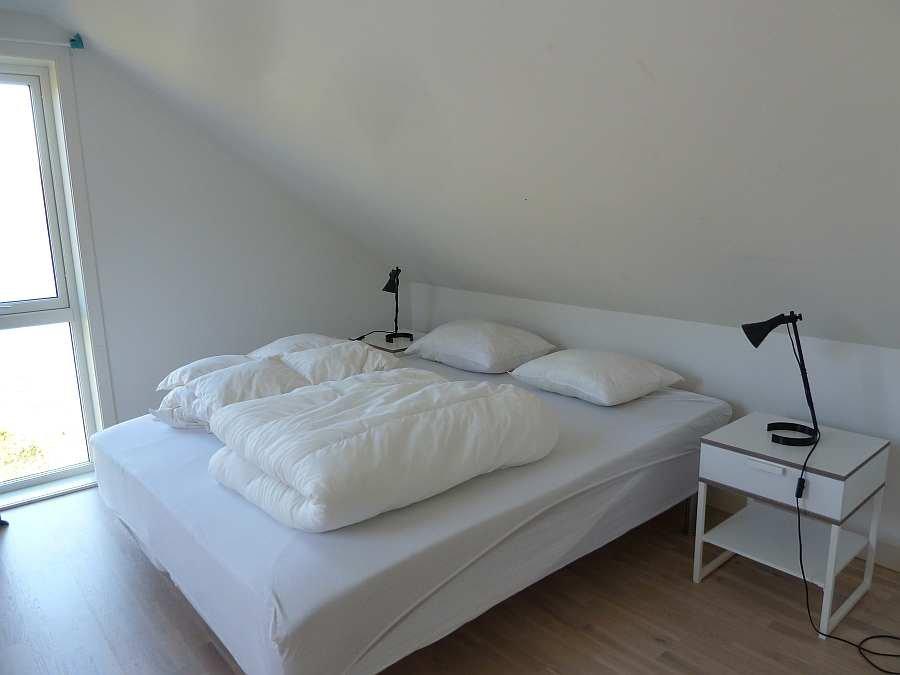 Das Schlafzimmer mit 1 Doppelbett und 1 Einzelbett im Obergeschoß - mit Fjordblick