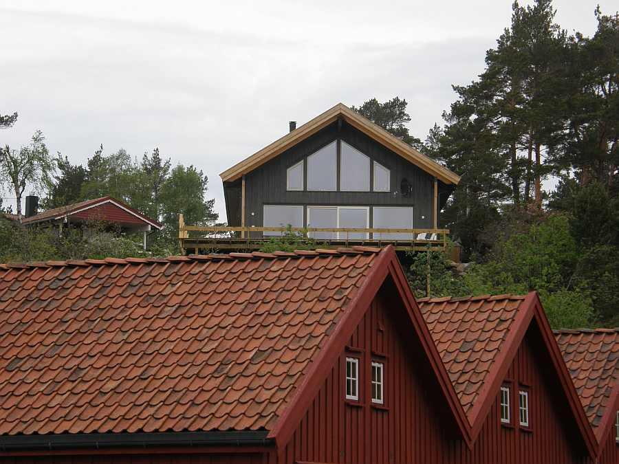 Das Ferienhaus Urvikodden liegt direkt vor einem kleinen Bootshafen - im Vordergrund Bootshäuser, dahinter das Ferienhaus