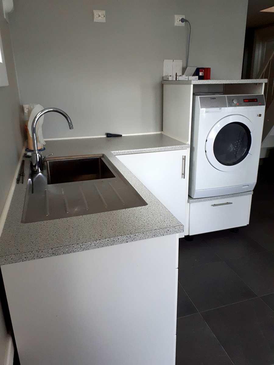 Die Waschküche des Hauses mit Spüle und Waschmaschine