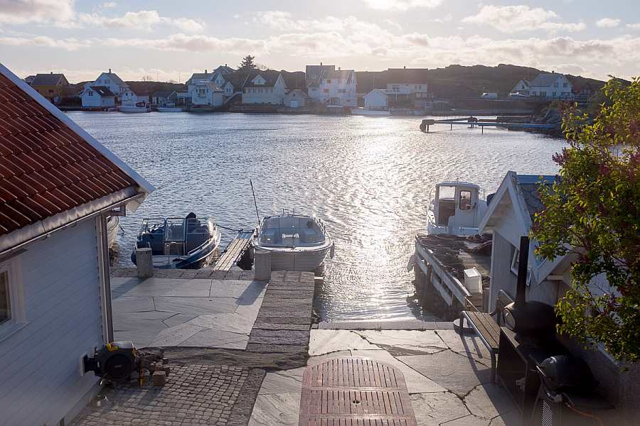 Blick aus dem Haus auf das Wasser und die Terrasse mit  Gasgrill