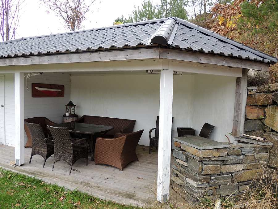 Sitzgruppe im überdachten Bereich der Terrasse mit Grill