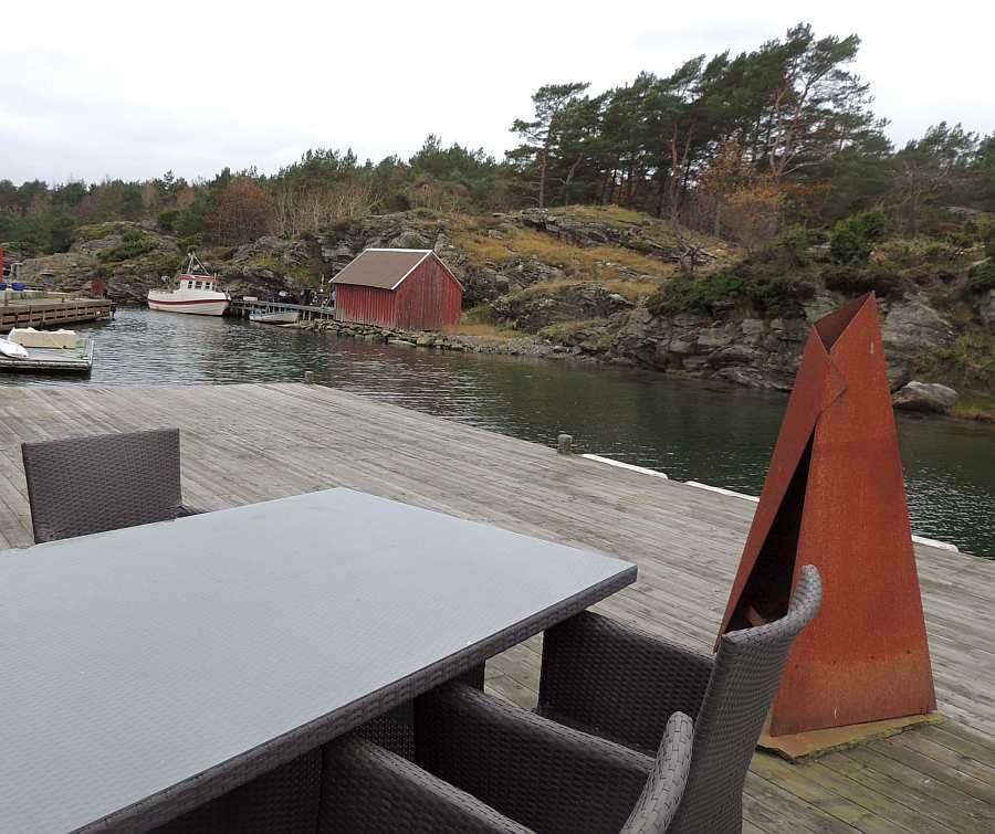 Die große Terrasse/Steg am Wasser. Hier gibt es mehrere Sitzgruppen. Hier im offenen Bereich mit  Aussenkamin