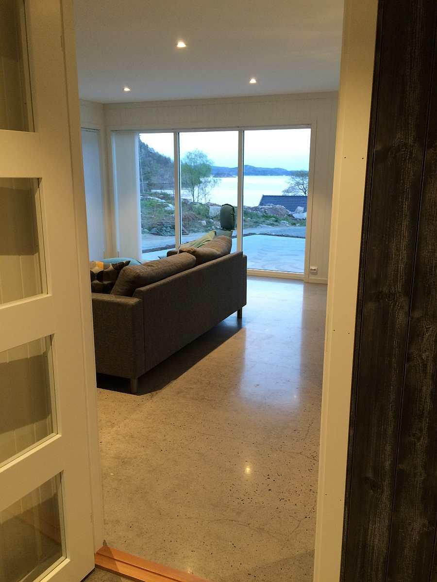 Blick vom Flur in das Wohnzimmer im Erdgeschoß. Vom Wohnraum hat man einen direkten Blick auf den Fjord