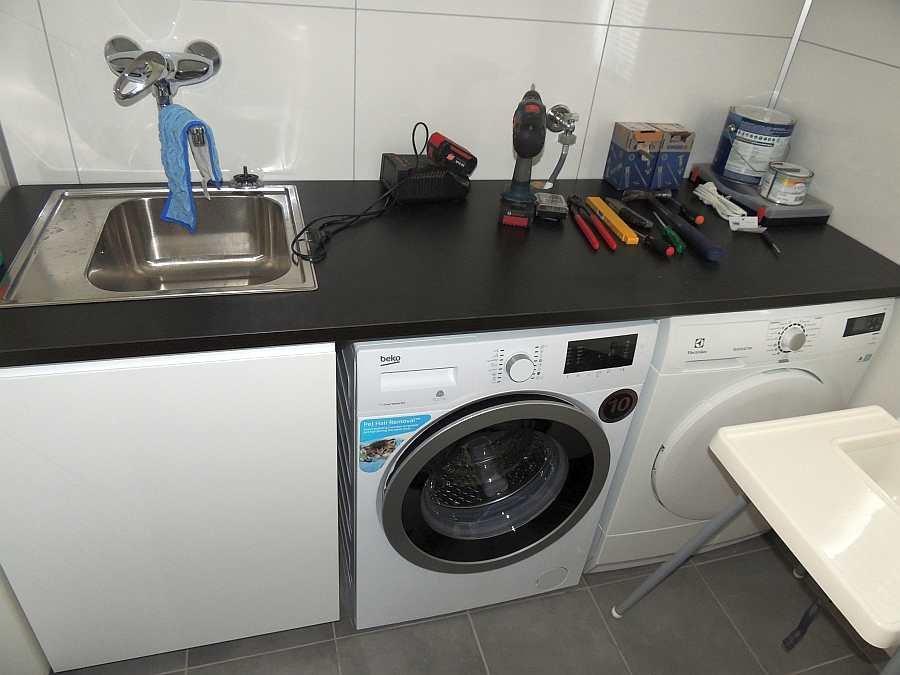 Die Waschküche des Hauses mit Spüle, Waschmaschine und Trockner