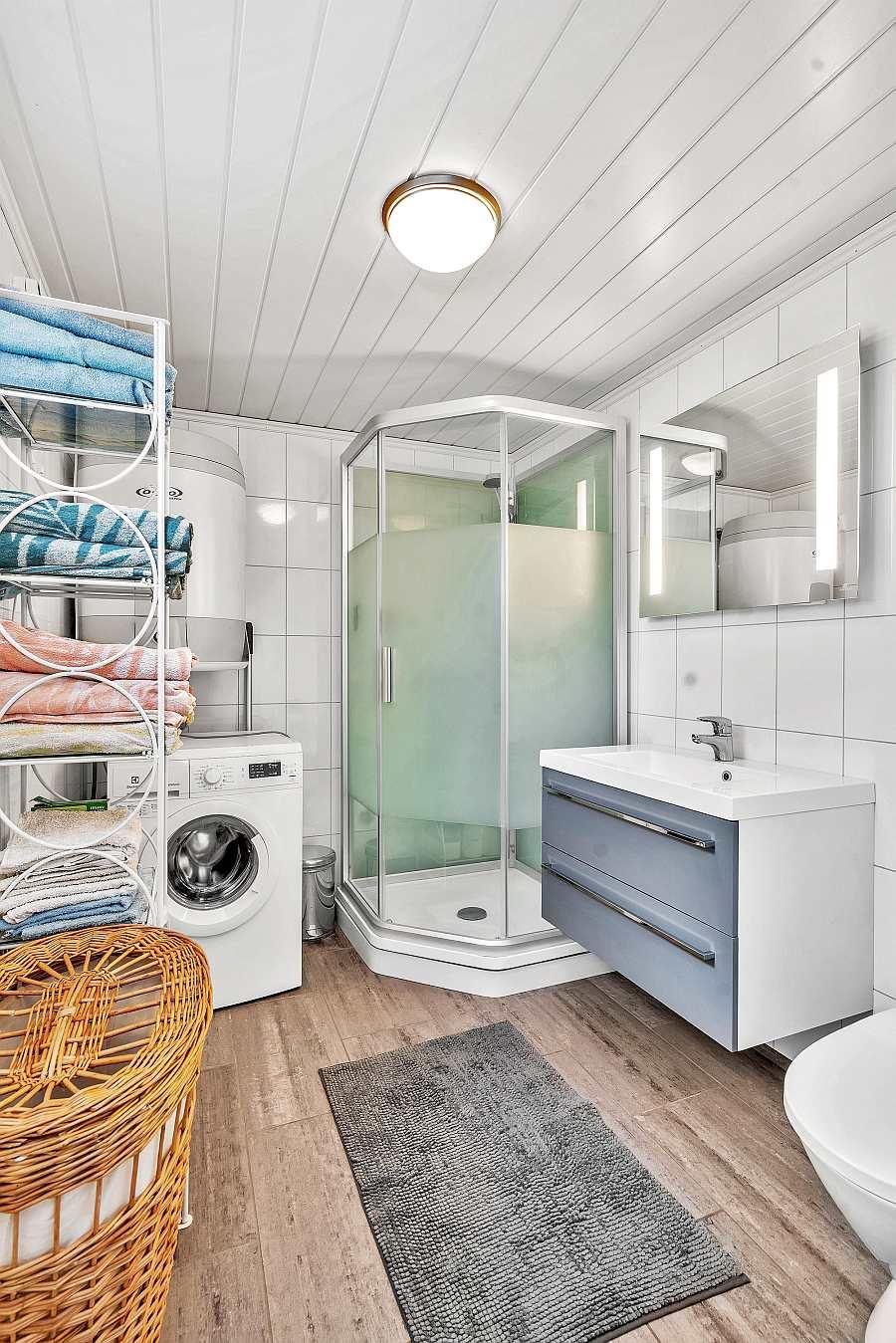 Das Badezimmer des Ferienhauses mit Dusche, WC und einer Waschmaschine