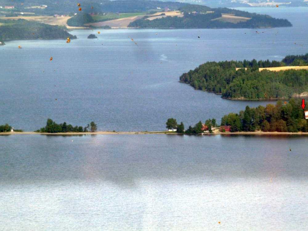 Blick auf die Landzunge 'Sandstangen', die sich weit in den See Øyeren erstreckt. Der rote Pfeil zeigt die Lage des Hauses