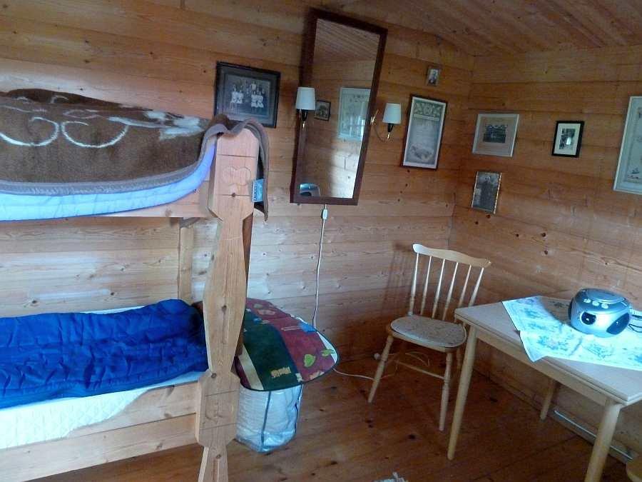 Im Schlafhaus steht ein Etagenbett, ein kleiner Tisch mit Stühlen und ein weiterer Kühlschrank zur Verfügung