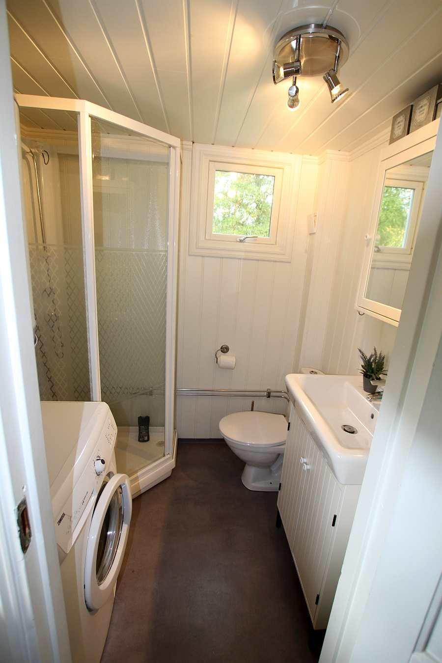 Das Badezimmer mit Dusche, Waschbecken, WC und Waschmaschine