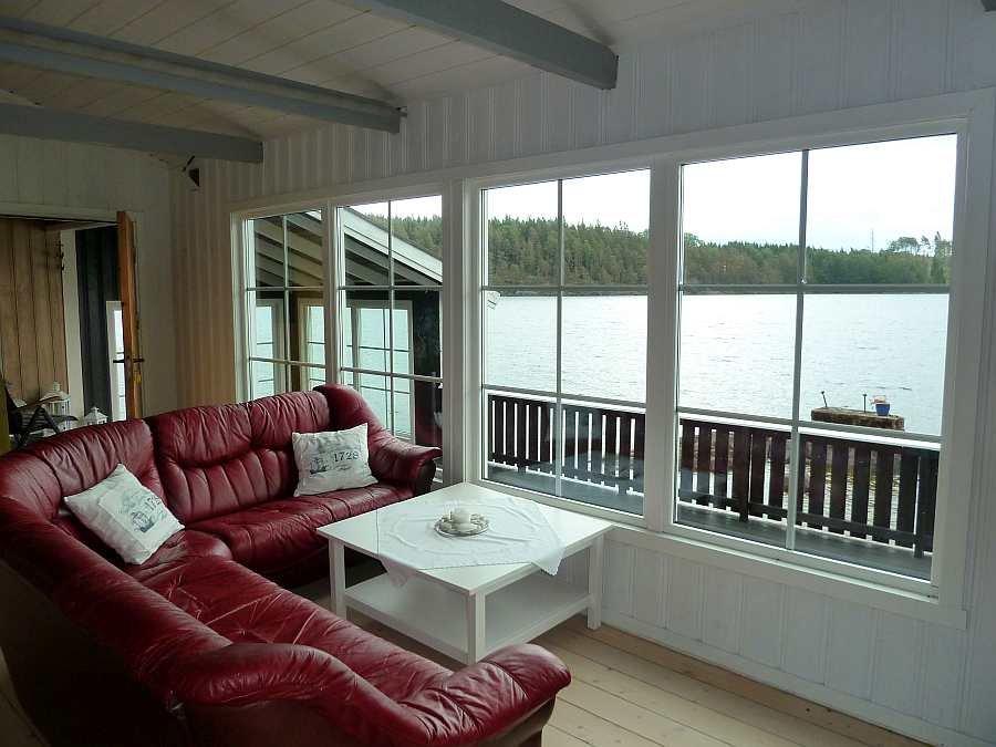 Von der Sitzecke hat man durch die großen Panoramafenster einen 180 Grad Panoramablick auf den See