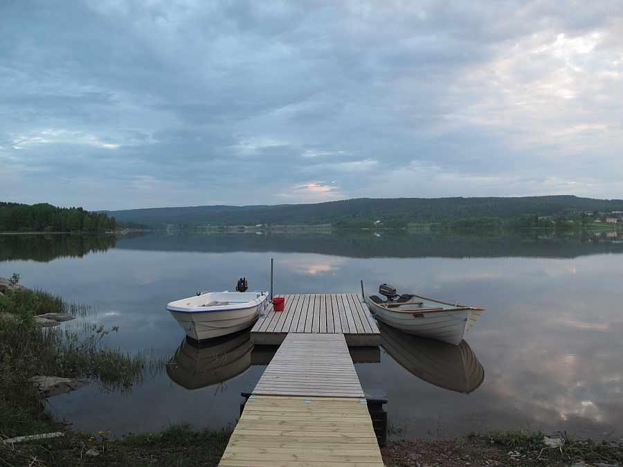 Blick vom Ferienhaus auf den Bootssteg und den See