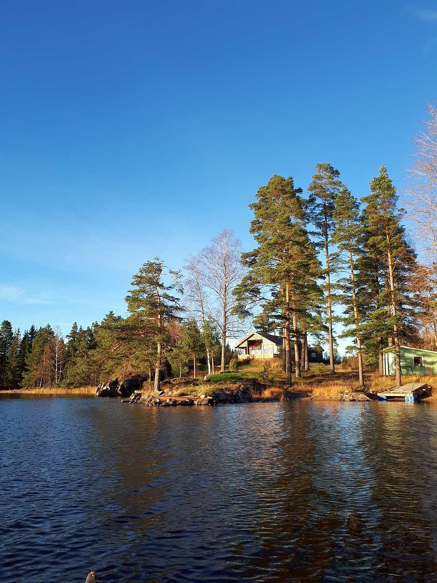 Blick vom Wasser auf das große Naturgrundstück des Hauses. Rechts der eigene Bootssteg