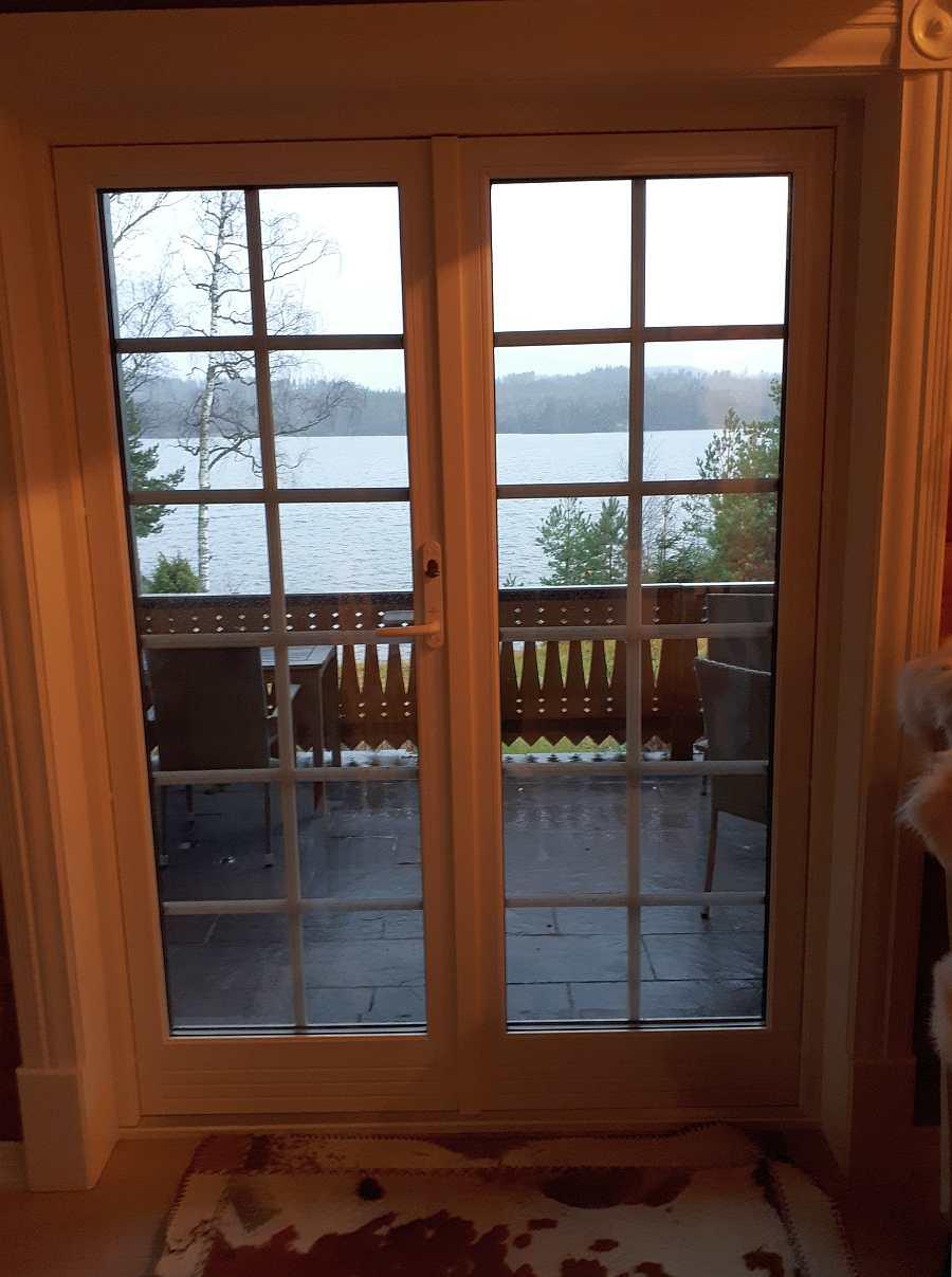 Blick vom Wohnbereich auf die Veranda und den See