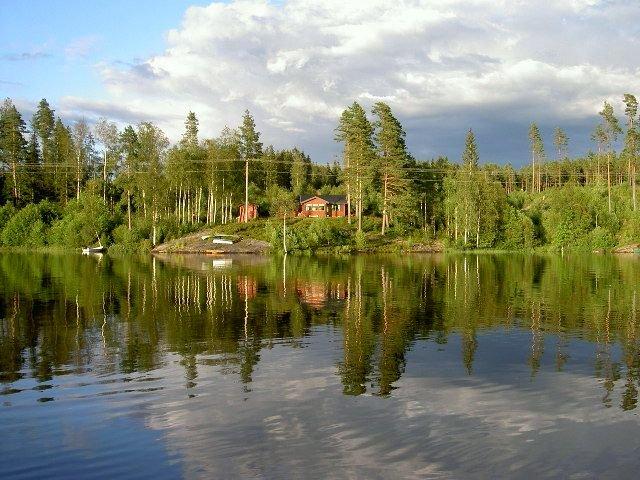 Blick vom Wasser auf das Grundstück des Ferienhauses Lerbukta