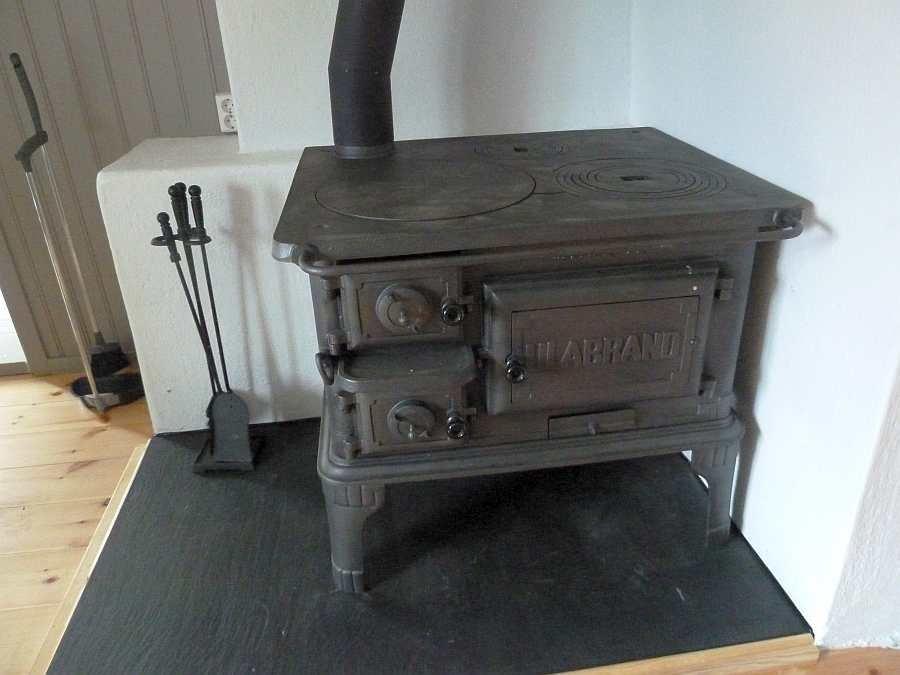 Die antike Küchenhexe mit Holzofen schafft besondere Behaglichkeit in der Küche