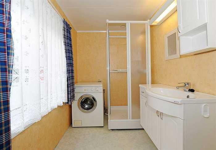 Eines der beiden Badezimmer des Ferienhauses - hier mit Dusche, Waschbecken und Waschmaschine