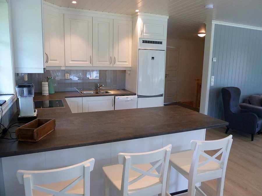 Ein Küchentresen mit Barhockern trennt die offene Küche vom Wohnbereich ab.