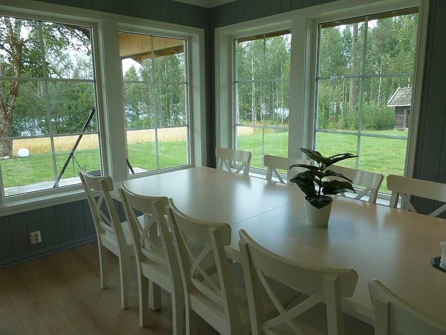 Auch vom Esstisch kann man durch die großen Fenster direkt in den eigenen Garten und auf den See schauen